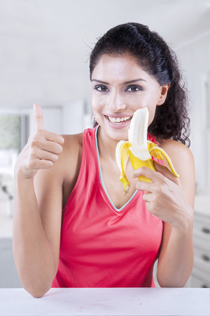 comiendo platano: mujer joven feliz disfruta de plátano fresco en casa mientras sonriendo y mostrando el pulgar para arriba en la cámara Foto de archivo