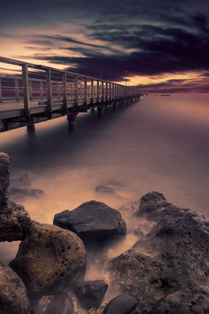 beach view: Picture of a beautiful long wooden jetty with rock on the beach at sunset time
