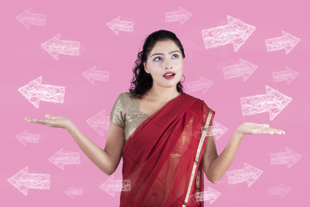 uncertain: Uncertain Indian woman in traditional dress looking at arrows on pink background