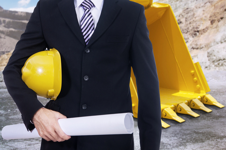 machinery: Close up of male engineer with blueprint and backhoe on the construction site