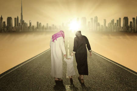 parents with baby: Rear view of arabic family walking on the highway while holding hands Stock Photo