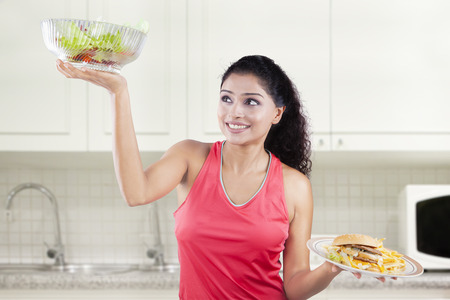 comparing: Picture of Indian woman comparing a bowl of fresh salad and hamburger in the kitchen at home