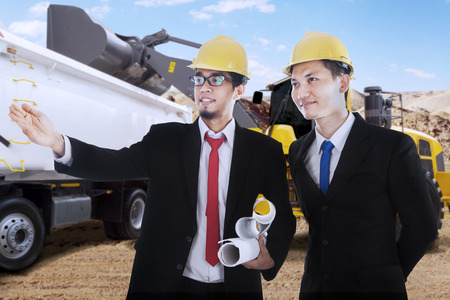 heavy equipment operator: Portrait of two male engineers observe the construction site while wearing helmet and hold blueprint