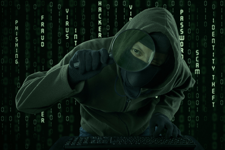 Internet Theft - a man wearing a balaclava looking at computer screen using magnifying glass