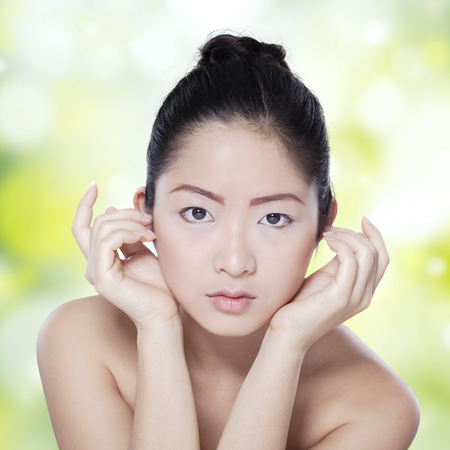 healthy looking: Healthy skin face of young asian model looking at the camera, shot against blur background