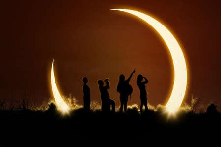 sol y luna: Silueta de cuatro personas viendo un eclipse solar en la naturaleza Foto de archivo