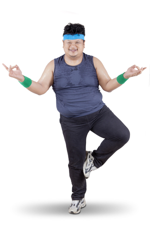 asian adult: Portrait of young overweight person wearing sportswear and doing workout in studio, isolated on white background