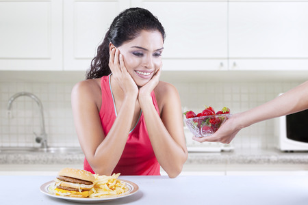 asian foods: Photo of Indian woman sitting in the kitchen and looks want to eat strawberry rather than hamburger Stock Photo