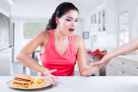 refuse: Photo of Indian woman taking healthy strawberry and refuse unhealthy hamburger in the kitchen