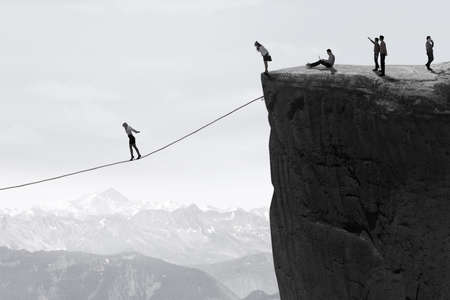 woman rope: Image of businesspeople walking on the gap one by one with a rope