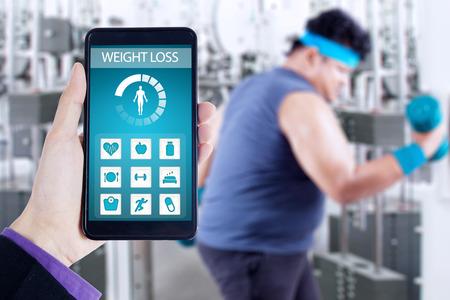 Mano que sostiene la aplicación de monitoreo de la salud en el teléfono inteligente, tiro con persona con sobrepeso haciendo ejercicios en el gimnasio