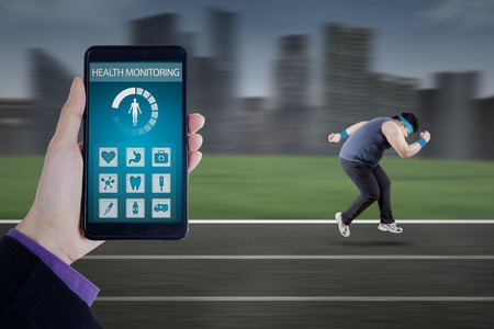 screen shot: Hand holding a smartphone with health monitoring apps on the screen, shot with overweight person running on the track Stock Photo