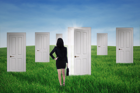 prospect: Business woman standing in front of opportunity doors on the green field