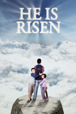 jesus standing: Image of two cute children standing on the cliff with their dad and text he is risen on the sky Stock Photo