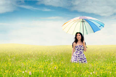 Pretty young woman walking on the meadow while holding a rainbow umbrella, shot in the springtime photo