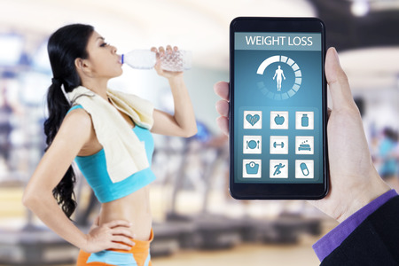 screen shot: Hand holding a mobile phone with health monitoring application on the screen, shot with young woman drinking water at gym