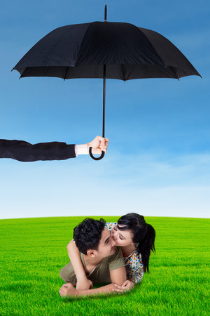 asian family outdoor: Photo of two young couple lying on the meadow under umbrella. Life and family insurance concept