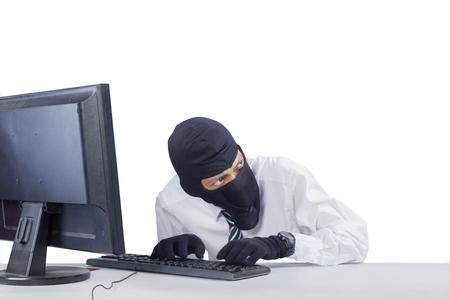 ladron: Foto de ladrón llevaba máscara, mientras que la piratería una computadora para robar información, aislado en fondo blanco Foto de archivo