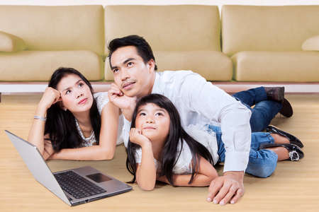 family sofa: Image of three member of happy family with laptop computer, lying on the floor while daydreaming near the sofa at home