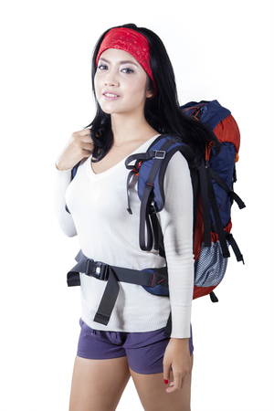 girl sport: Young Asian woman standing in the studio while carrying a hiking bag and smiling at the camera, isolated on white background