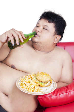couch potato: Portrait of young overweight man sitting on the sofa while enjoying fresh beer and burger Stock Photo