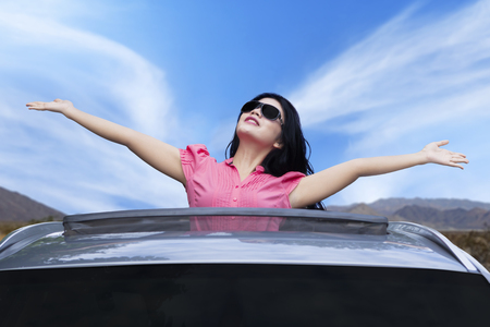 sunroof: Picture of cheerful young woman wearing sunglasses and raised hands on the sunroof of the luxury car