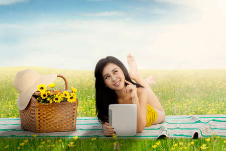 woman lying: Beautiful young woman picnic on the meadow and lying on the mat while holding a digital tablet
