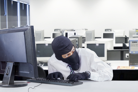 watchful: Portrait of watchful robber wearing balaclava while stealing information in the office room