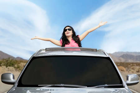 sunroof: Portrait of pretty woman wearing sunglasses standing in the car and raised hands on the sunroof