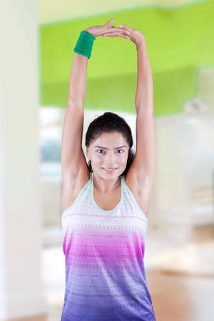 woman stretching: Portrait of pretty young indian woman stretching her arms to warm up in the fitness center Stock Photo