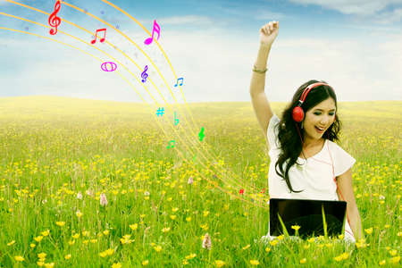 Joyful female model sitting on the meadow while listening music with laptop and headphone photo