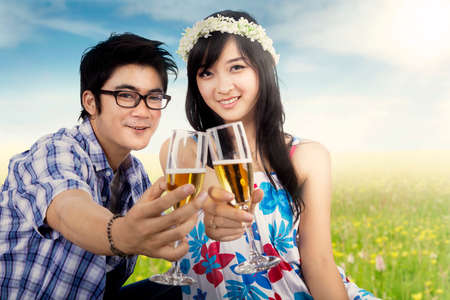 drinking alcohol: Portrait of two young Asian lovers drinking champagne together on the meadow at springtime