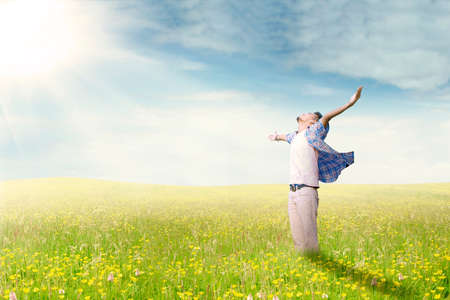 praise god: Young man standing on the meadow while enjoying his happy time and raise hands, shot in the springtime Stock Photo