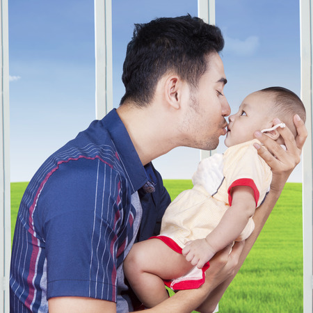 0 3 months: Portrait of young father holds a three months baby near the window and kiss the babys lips Stock Photo