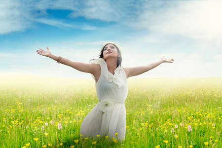 Beautiful young woman with outstretched hands enjoying freedom on the meadow in springtime photo