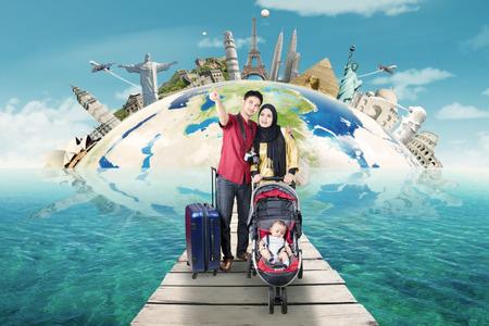Dos padres con el bebé viaje macho a los monumentos del mundo mientras se camina sobre el puente en el mar Foto de archivo