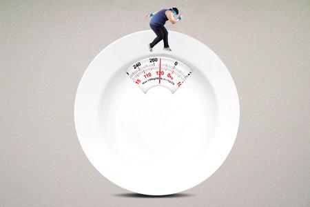 Afbeelding van de persoon met overgewicht proberen om gewicht te verliezen door het uitvoeren van op de schaal gevormde een leeg bord