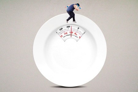 lose weight: Image of overweight person try to lose weight by running on the scale shaped an empty plate