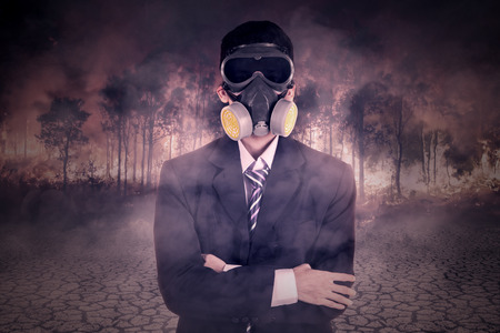 environment protection: Male entrepreneur wearing gas mask and standing in front of forest fire