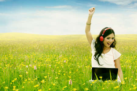 Picture of cheerful young woman enjoy music with laptop and headphone while sitting on the meadow at springtime photo