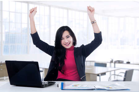 excited woman: Cheerful young businesswoman celebrating her success while working with laptop in the office