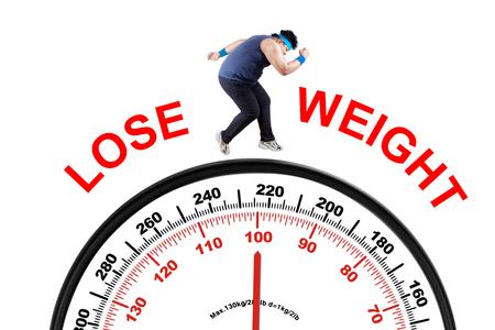 Foto des jungen übergewichtigen Person mit Gewicht zu verlieren Text, läuft über Skala. Isoliert auf weißem Hintergrund Standard-Bild