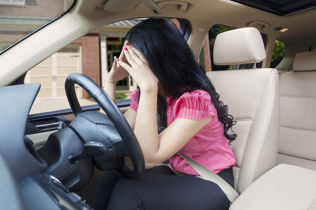 Picture of frustrated young woman having problems with her car, holding her head while driving