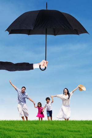 convivencia familiar: Foto de familia alegre que se ejecuta en el prado mientras mantiene las manos bajo el paraguas. La vida y la familia de seguro