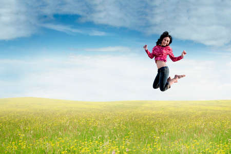a meadow: Photo of beautiful young Asian woman jumping on the meadow at springtime Stock Photo