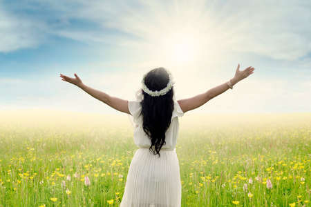 Back view of young woman standing on the meadow with outstretched hands, shot in springtime photo