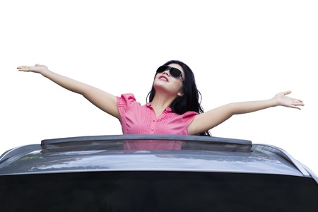 sunroof: Picture of successful young businesswoman standing in the car and raised hands on the sunroof while wearing sunglasses