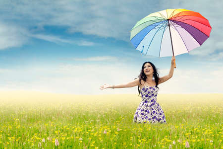 Picture of beautiful young woman holding colorful umbrella on the meadow, shot at springtime photo