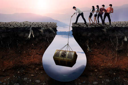 pulling money: Group of businesspeople finding a treasure chest in the soil and try to get it together Stock Photo