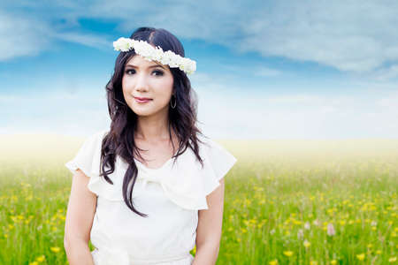 Beautiful Asian woman standing on the meadow with flower crown on her head, smiling at the camera photo